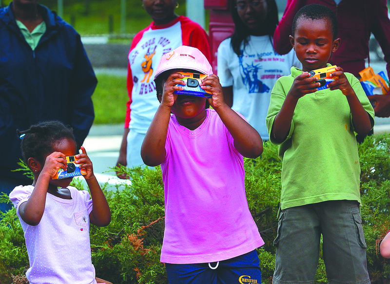 Deborah Yennah, 3, Tatiana Walker , 5, and Joshua  Yennah, 5, of Everett snap photos of skaters with their free cameras.  They came over after hearing noise while picinicing with the Emanuel Baptist church of Malden. The photo and skateboarding event was a fundraiser for the  New Melrose Skate Park Saturday at  Hunt's Photo and Video.(6/28/08)