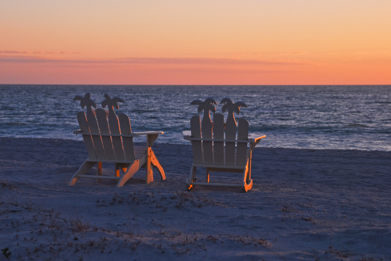 Palm tree chairs at sunset
