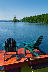 A pair of adirondack chairs sit atop a raft in Newfound Lake, with views to little Loon Island.