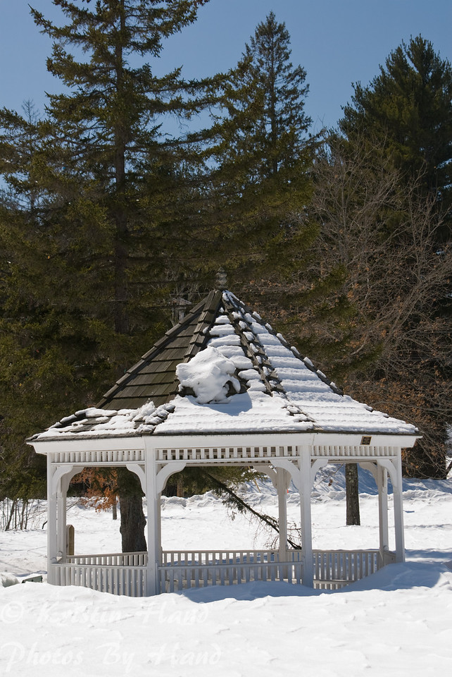 Designs of snow covered gazebo in winter, with interesting architectural accents and snow patterns on roof.