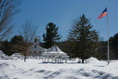 Gazebo, American flag, and meeting house on town common, with plenty of snow.