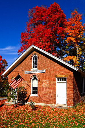 Green District One room schoolhouse, circa 1850, surrounded by fall color in trees, Canterbury Village, NH.