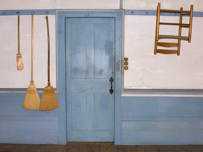Brooms and chair hanging on wall pegs, rustic blue & white paint scheme at historic Canterbury Shaker Village.