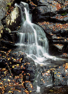 Waterfall flows over rocks in a white veil,with  autumn leaves, Rumney, NH.