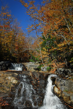 Vertical view of multiple waterfalls surrounded by bedrock & fall colors, blue sky.