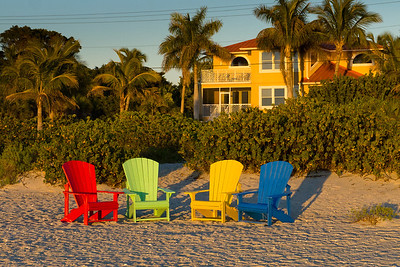 Last light on gathering of adirondack chairs at the beach.