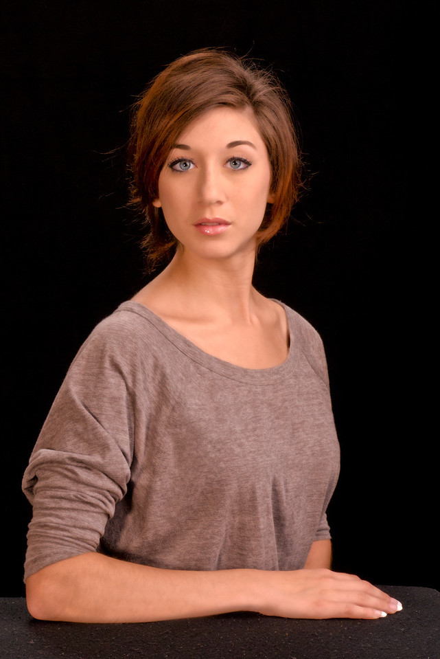 Model with beautiful eyes poses in a understated blouse.