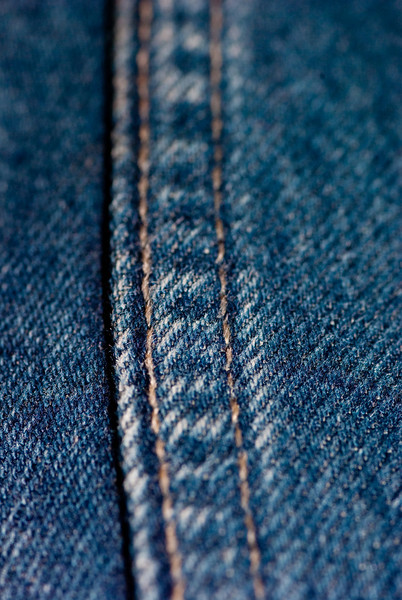 Macro of the leg seam on a pair of blue denim jeans with gold stitching