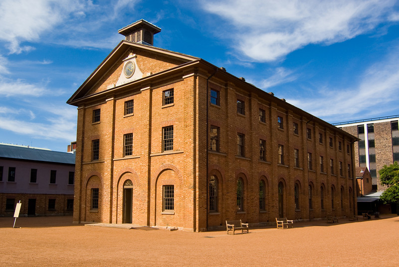 A wide-angled view of the Hyde Park Barracks Museum in Sydney under a cloudy blue sky. The barracks was originally used to house convicts in colonial times