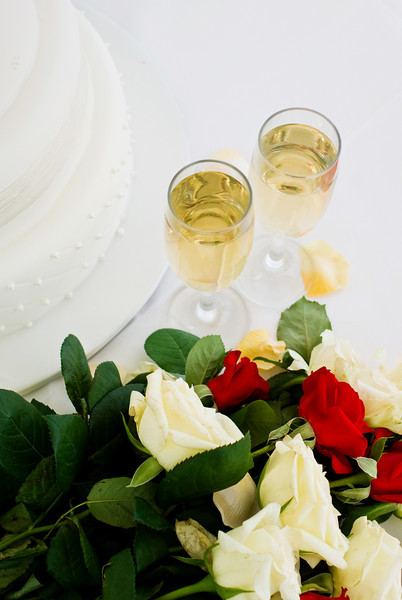 Bridal Bouquet of Roses With Wedding Cake and Glasses of Champagne