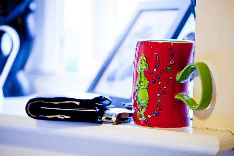 Coffee mug, wallet ad watch on a window sill.