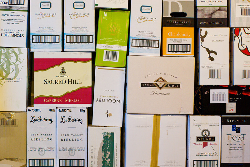 A pile of discarded wine boxes outside a liqour store.