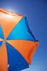 Shade from the hot sun under a colourful beach umbrella