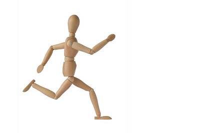 A wooden mannequin in a running pose, isolated with clipping path
