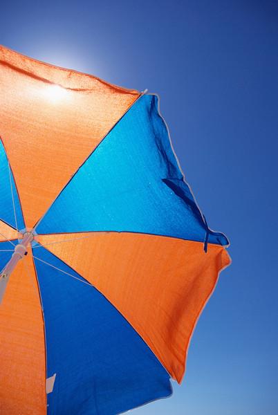 Shade from the hot sun under a colourful beach umbrella