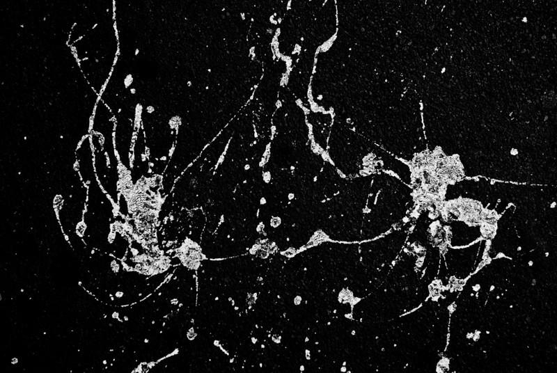White Paint Splattered on a Black Wall