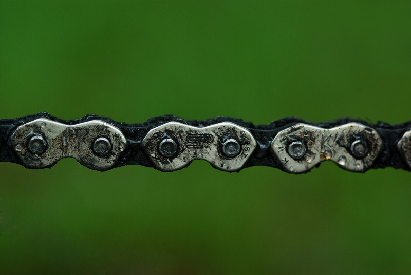 Links of a bicycle chain on the front sprocket with raindrops