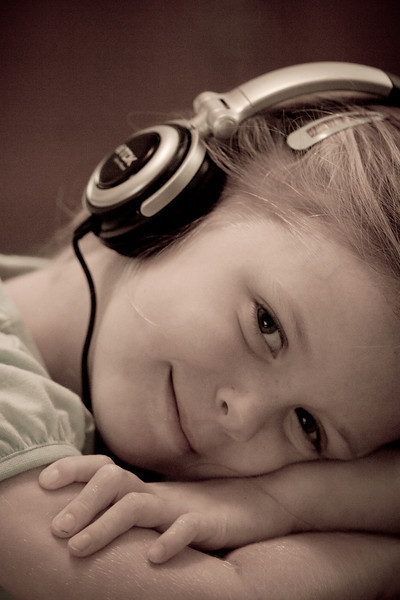 Eleanor listening to music with headphones.<br /> <br /> This has to be one of my favourite photos of Eleanor. It was totally unprompted. I just ccrept up on her while she was listening and she smiled for me. Shot indoors without flash at f/2.8 and ISO1000.