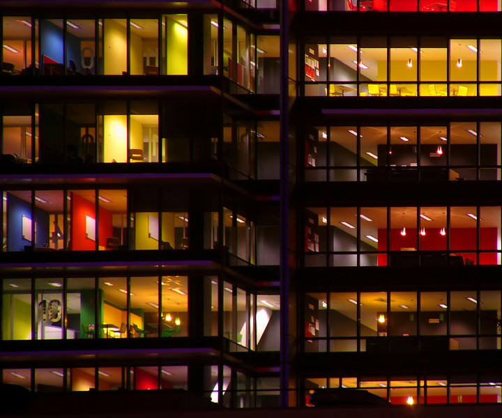 Some colourful office in a highrise office block at night