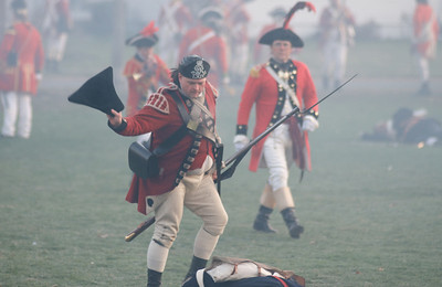 041513, Lexington, MA - A British regular army reenactor throws the hat of a fallen minuteman on the man's body after driving the militia off the town common during the reenactment of the Battle of Lexington. Photo by Ryan Hutton