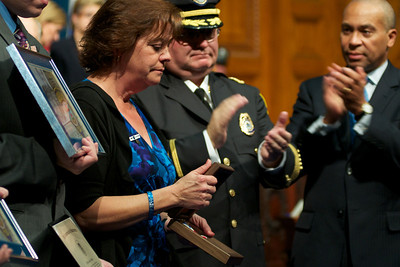 Nov. 18, 2011, Boston, MA - The widow of Woburn police Officer John Maguire displays his posthumous Medal of Honor at the George L. Hanna Awards ceremony at the state house. Desiree Maguire, left, was joined by Woburn Police Chief Robert J. Ferullo Jr., center, and Gov. Deval Patrick, right. Maguire was killed during a robbery last year. By Ryan Hutton