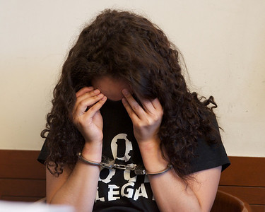 070912, Boston, MA - Maria Guzman, 28, of Jamaica Plain, covers her face during her arraignment on drug charges in Boston Municipal Court on Monday. Herald photo by Ryan Hutton