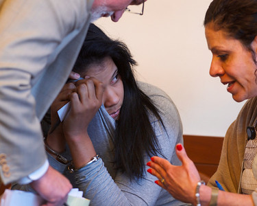 070912, Boston, MA - Mayra Valdez Martinez, 24, tries to cover her face while talking to her lawyer and the court translator during her arraignment on drug charges in Boston Municipal Court on Monday. Herald photo by Ryan Hutton