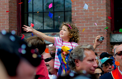 090212, Lawrence, MA - A young girl reaches for confetti as the statues of Saints Filadelfo, Alfio and Cirino are brought out of  Corpus Christi Parish on Essex Streer under a sea of confetti as part of the three-day-long Feast of the Three Saints. Photo by Ryan Hutton