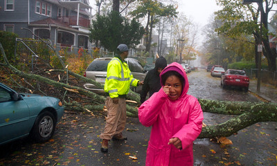 102912, Boston, MA - DPW  Districts 10 and 2 Supervisor Darrell Kaiser, 38, ushers people over a tree blocking Ruthven Street that was brought down by Hurricane Sandy's winds. Photo by Ryan Hutton