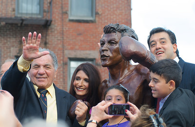102012, Boston, MA - Former Welterweight Champion Tony DeMarco, left, stands with his statue just after it was unveiled at the intersection of Hanover and Cross Streets. On the right is Phil Privitera, president of the Privitera Family Charitable Foundation which funded its construction, and his children. Herald photo by Ryan Hutton