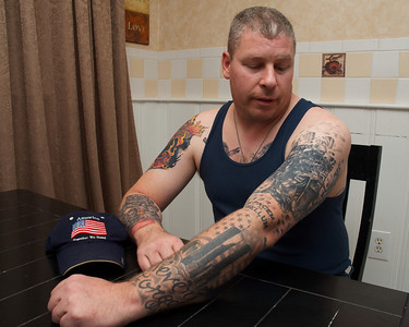 102512, Plainville, MA - US Army veteran Brian Parker shows off some of his tattoos, all of which reflect his time in the service. Herald photo by Ryan Hutton