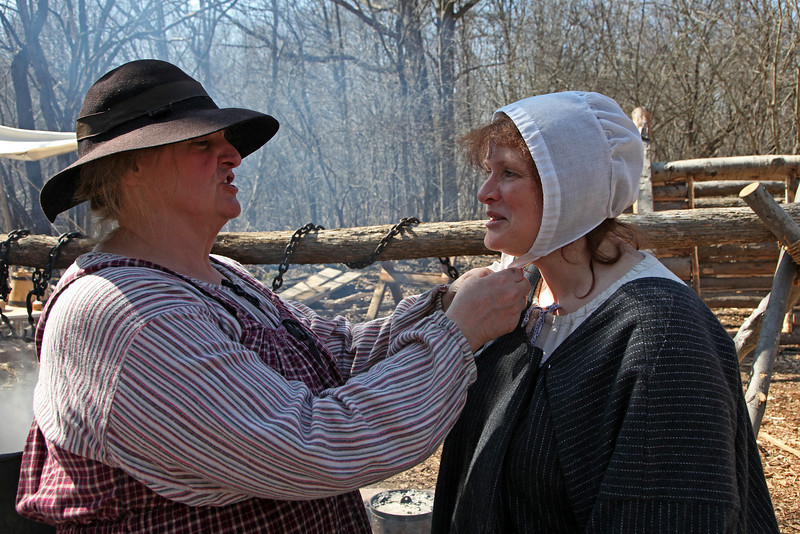 Master syrup maker ties hair piece on assistant, finger lakes.  2009