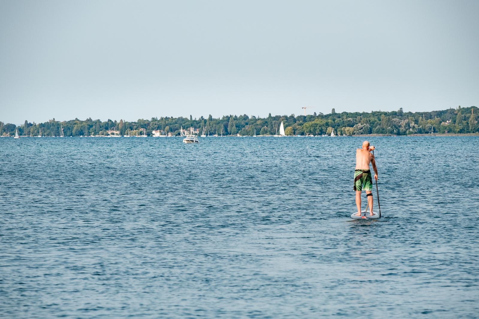 A man on a paddle board on lake Geneva