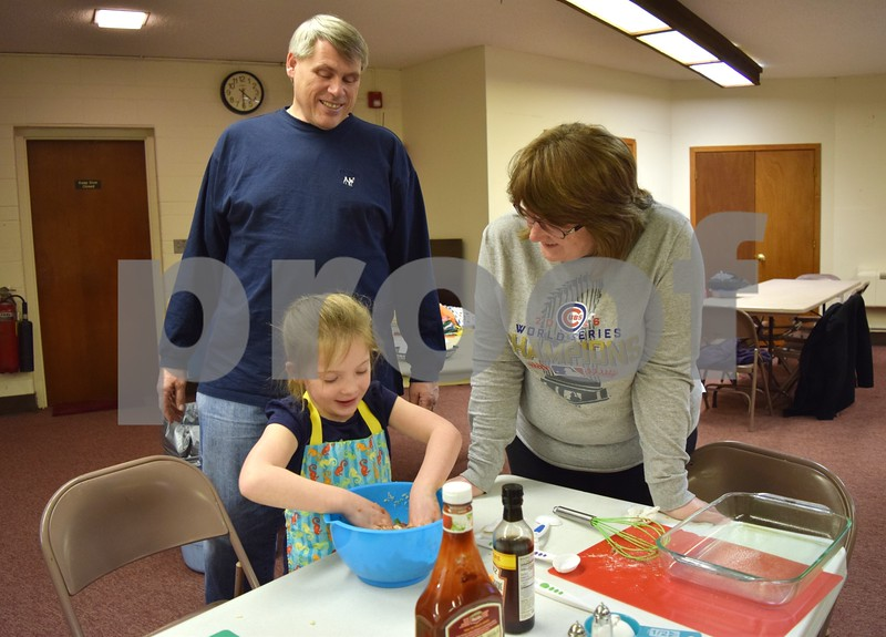 Katrina J. E. Milton - kmilton@shawmedia.com<br /> Dale and Deb Pelley of Genoa help their granddaughter, 5-year-old Addison Lyle, make meatloaf on Jan. 22 during a free family cooking class at Genoa Faith United Methodist Church. The family attended the class to learn new recipes and cooking techniques.