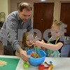 Katrina J. E. Milton - kmilton@shawmedia.com<br /> Charlie Perry (left) helps his 3-year-old daughter Lilly Perry and 5-year-old Addison Lyle, all of Genoa, make meatloaf on Jan. 22, during a free family cooking class at Genoa Faith United Methodist Church.