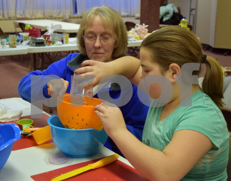 Katrina J. E. Milton - kmilton@shawmedia.com<br /> Louella Donovan of Sycamore (left) helped 10-year-old Steffini McDowell of Genoa add pomegranate seeds to a winter fruit salad on Jan. 22 during a free family cooking class at Genoa Faith United Methodist Church.