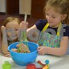Katrina J. E. Milton - kmilton@shawmedia.com<br /> Three-year-old Lilly Perry of Genoa watches as 5-year-old Addison Lyle of Genoa mixes ingredients for meatloaf on Jan. 22 during a free family cooking class at Genoa Faith United Methodist Church. More than 20 people attended the class.