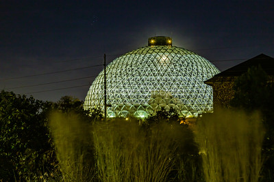 Desert dome at Henry Doorly Zoo Omaha Nebraska at night with the moon seen through the top of the dome. A collection of six stars to the left in the sky.