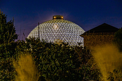 Desert dome at Henry Doorly Zoo Omaha Nebraska at night with the moon visible through the dome. A collection of six stars to the left in the night sky.