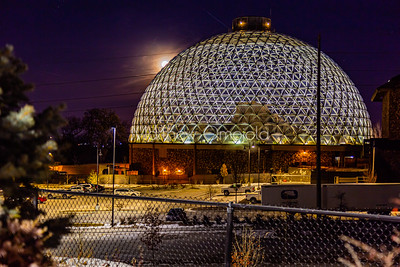 Desert dome at Henry Doorly Zoo Omaha Nebraska at night with the moon cresting by its left side.