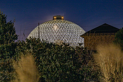 Desert dome at Henry Doorly Zoo Omaha Nebraska at night with the moon visible through the top of the dome.