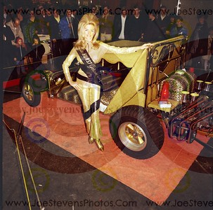 "This car that Linda Vaugh is posing next to for photographer, Joe Stevens, is the George Barris ""Bed Buggy"" Kustom Hot Rod with luscious leopard print seats & shimmering gold lemay.  A perfect match for Miss Hurst Golden Shifter's golden lemay jumpsuit."