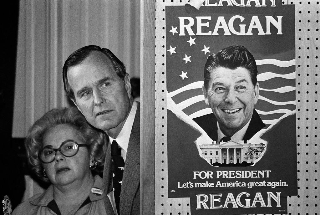. FILE - In this March 4, 1980 file photo, George H.W. Bush and an unidentified woman peek around a partition with a poster of Ronald Reagan, one of his opponents for the Republican party presidential nomination, before he speaks in Columbia, S.C. Bush has died at age 94. Family spokesman Jim McGrath says Bush died shortly after 10 p.m. Friday, Nov. 30, 2018, about eight months after the death of his wife, Barbara Bush. (AP Photo, File)