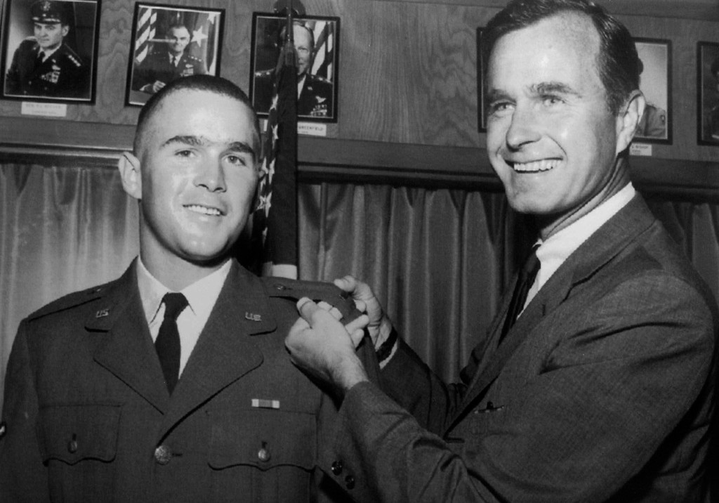 . FILE - In this 1968 file photo provided by the Texas National Guard, George H.W. Bush, right, is about to pin a lieutenant bar on his son, George W. Bush, after the younger Bush was made an officer in the Texas Air National Guard in Ellington Field, Texas. Bush died at the age of 94 on Friday, Nov. 30, 2018, about eight months after the death of his wife, Barbara Bush. (AP Photo, File)