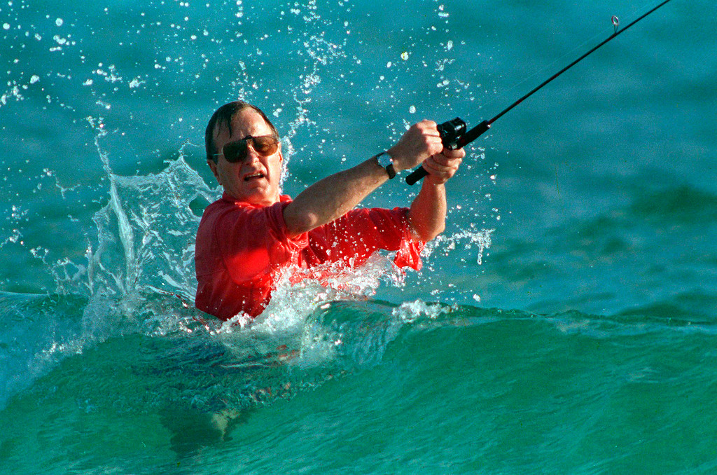 . FILE - In this Nov. 12, 1988, file photo, waves splash on then-President-elect George H.W. Bush as he casts a line while fishing in Gulf Stream, Fla. Bush died at the age of 94 on Friday, Nov. 30, 2018, about eight months after the death of his wife, Barbara Bush. (AP Photo/Kathy Willens, File)