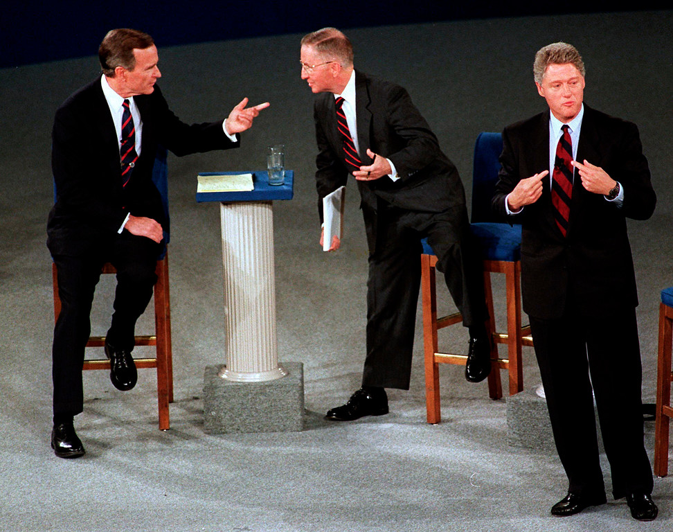. FILE - In this Oct. 15, 1992, file photo, President George H.W. Bush, left, talks with independent candidate Ross Perot as Democratic candidate Bill Clinton stands aside at the end of their second presidential debate in Richmond, Va. Bush died at the age of 94 on Friday, Nov. 30, 2018, about eight months after the death of his wife, Barbara Bush. (AP Photo/Marcy Nighswander, File)