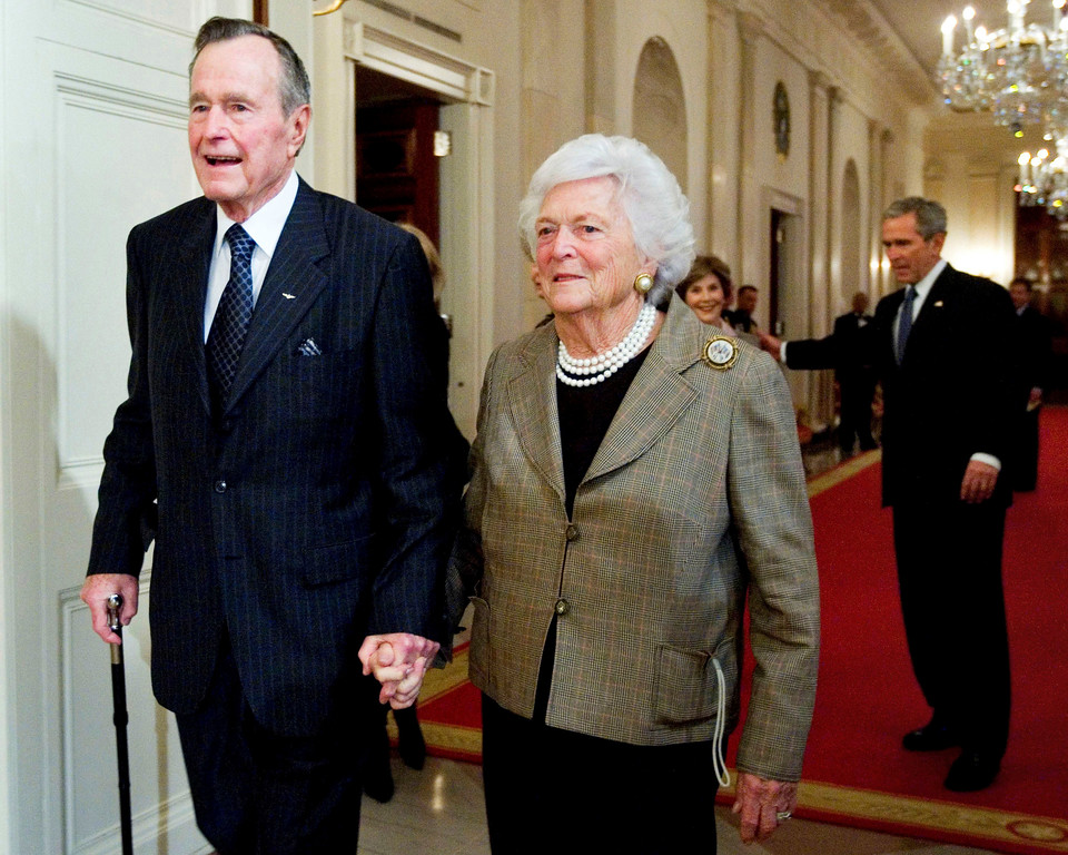 . FILE - In this Jan. 7, 2009, file photo, former President George H. W. Bush, left, walks with his wife, former first lady Barbara Bush, followed by their son, President George W. Bush, and his wife first lady Laura Bush, to a reception in honor of the Points of Light Institute, in the East Room at the White House in Washington. Bush died at the age of 94 on Friday, Nov. 30, 2018, about eight months after the death of his wife, Barbara Bush. (AP Photo/Manuel Balce Ceneta, File)
