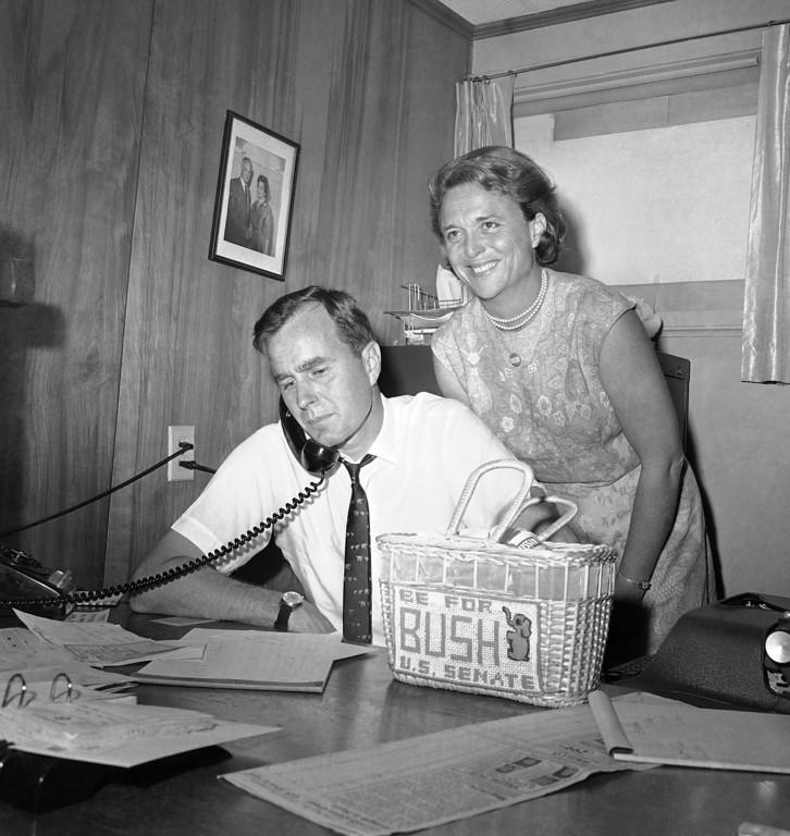 . FILE - In this June 6, 1964, file photo George H.W. Bush, candidate for the Republican nomination for the U.S. Senate, gets returns by phone at his headquarters in Houston, as his wife Barbara, smiles at the news. Bush died at the age of 94 on Friday, Nov. 30, 2018, about eight months after the death of his wife, Barbara Bush. (AP Photo/Ed Kolenovsky, File)