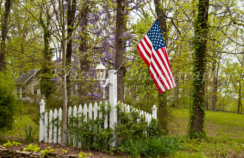 An American flag with small white fence in Macon, Georgia, USA.