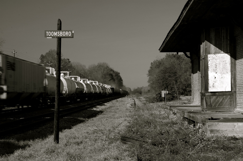 """Toomsboro, GA (Wilkinson County) 2007<br /> <br /> The Central of Georgia Railroad line between Savannah and Macon runs through Wilkinson County and was built between 1835-1843. When the road was being surveyed, the citizens of Irwinton did not want it to run through their town for fear that the trains would run over all their livestock and children - the same reluctance, or hindsight, could be seen in Oglethorpe County's Maxeys and Lexington. The stations were originally known by their numbers such as """"15,""""  """"16,"""" and """"17,"""" standing for Emmitt, Wriley and Gordon respectively. <br /> <br /> At first, there was no station at Toomsboro but at Emmitt only 1 mile to the east. Toomsboro grew later; the first post office was established in 1859 and the town was incorporated in 1904. It seems to have been a thriving town and the massive Victorian Hotel, a cotton warehouse, and a few commercial buildings are still standing, silent reminders of the prosperity of the past. Today, Toomsboro has a population of 622."""